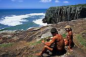 Torres, Rio Grande do Sul State, Brazil. man in shorts, girl in bikini sitting on the rocks by the sea.