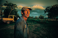 A farm hand keeping one eye to the weather on David Walkers Cattle station.  They are bringing helicopters in next day to muster cattle and move them to higher ground.  The landscape fills with water during this season and the cattle get bogged and die if  they aren't moved out.  They are gathered in staging areas with helicopters and then moved by truck to higher ground.