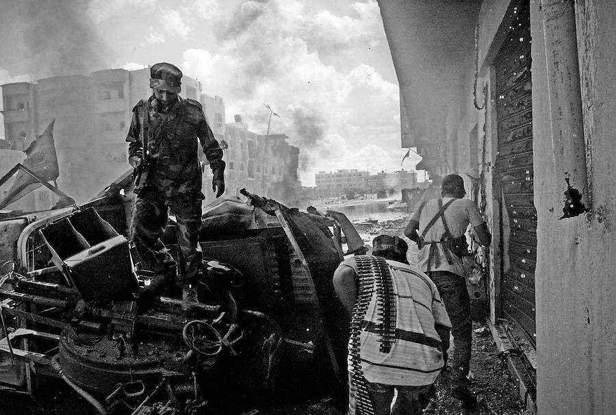 Anti-Gaddafi fighters on a battle-torn street in Sirte, Libya.