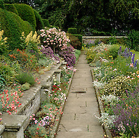 Flowerbeds in full bloom line the flagged stone path in this Scottish country garden