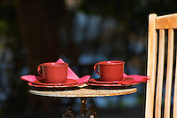 A table with two red coffee cups and a wooden teak deck garden chair Clos des Iles Le Brusc Six Fours Cote d'Azur Var France