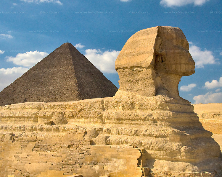 """Giza, Cairo, Egypt -- Viewed from the side, the Great Sphinx, part of the funerary temple of Khafre (Kephren), sits in the foreground with the """"Great Pyramid"""" of Khufu (Cheops) in the background. © Rick Collier / RickCollier.com."""