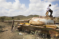 Somaliland. Awdal province. Gorayo Awl is a small village. While reading a book, a young muslim black teenager sits on a gun turret of a destroyed russian made military tank which was destroyed during the war with Somalia. After a long war, on May 18, 1991, the major Somaliland clan, namely Isaqs, declared independence from the Somalia. Somaliland is an unrecognized de facto sovereign state located in the Horn of Africa.  © 2006 Didier Ruef
