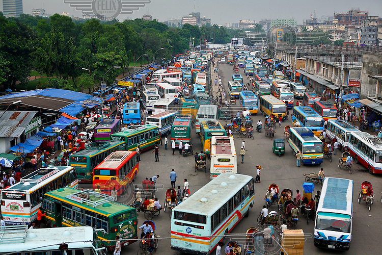 A road crowded with buses, rickshaws and people in Gulistan...