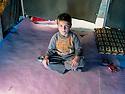 Iraq 2013 .Domiz Refugee Camp: Nechirvan,7 years old in the tent where his family of 6 members is living with 9 guests. Irak 2013.Camp de refugies de Domiz: Nechirvan, 7 ans, dans la tente de sa famille. Ils sont 5 plus 9 autres personnes, des invites temporaires, a partager cet abri.
