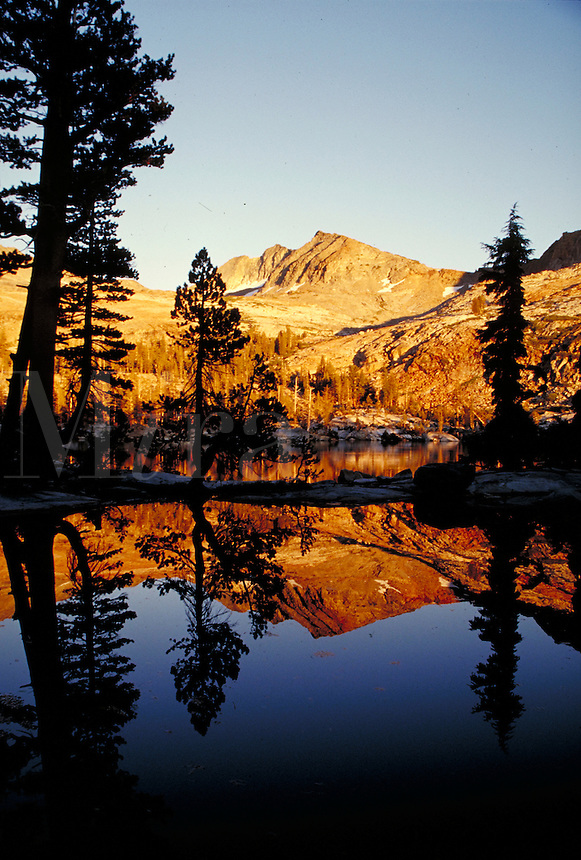 lower Ottaway Lake at dusk in wilderness landscape showing reflection of mountains in lake. California, Yosemite National Park.