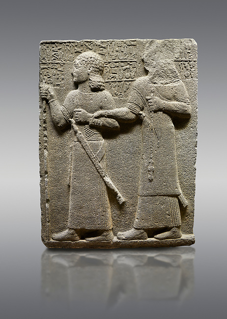 """Picture & image of Hittite monumental relief sculpted orthostat stone panel of Royal Buttress. Basalt, Karkamıs, (Kargamıs), Carchemish (Karkemish), 900-700 B.C. Anatolian Civilisations Museum, Ankara, Turkey.<br /> <br /> King Araras holds his son Kamanis from the wrist. King carries a sceptre in his hand and a sword at his waist while the prince leans on a stick and carries a sword on his shoulder. <br /> <br /> Hieroglyphs reads; """"This is Kamanis and his siblings. I held his hand and despite the fact that he is a child, I located him on the temple. This is Yariris' image"""".  <br /> <br /> Against a gray background."""