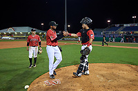Batavia Muckdogs pitcher Geremy Galindez (34) and catcher Andres Sthormes (44) celebrate closing out a NY-Penn League game against the Lowell Spinners on July 11, 2019 at Dwyer Stadium in Batavia, New York.  Batavia defeated Lowell 5-2.  Andrew Turner (9) looks on.  (Mike Janes/Four Seam Images)
