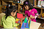Education preschool 4 year olds two girls playing together building with magnet tiles