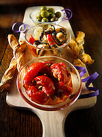 Italian party buffet food with sundried tomatoes, bread sticks, olives and  marinated wild mushrooms