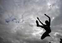 Female long jumper seen from below against stormy skies