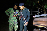 A military policeman and government environment ranger on an operation to confiscate illegally cut timber, during a night raid in rural northern Cambodia.