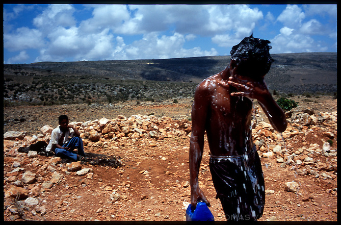 A boy washes himself from a roadside drum of water on the island of Socotra, Yemen on Wednesday, 18 May 2005.<br />