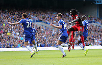 Pictured: Bafetimbi Gomis of Swansea (3rd L) takes a shot off target, against Nemanja Matic and Gary Cahill of Chelsea. Saturday 13 September 2014<br /> Re: Premier League Chelsea FC v Swansea City FC at Stamford Bridge, London, UK.