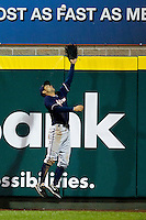 Anthony Seratelli (2) of the Northwest Arkansas Naturals attempts to make a catch at the right field wall during a game against the Springfield Cardinals on May 13, 2011 at Hammons Field in Springfield, Missouri.  Photo By David Welker/Four Seam Images.