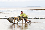 The Last Mudhorse Fishermen. UK 2008. The Sellick family, Stolford, Bridgewater Bay, Somerset. Adrian returning from the netts. Steep Holm island in Bridgewater Bay