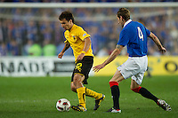 SYDNEY, AUSTRALIA - JULY 31, 2010: Scocco Ignacio Martin of AEK Athens evades Kirk Broadfoot of Rangers during the match between AEK Athens FC and Glasgow Rangers at the 2010 Sydney Festival of Football held at the Sydney Football Stadium on July 31, 2010 in Sydney, Australia. (Photo by Sydney Low / www.syd-low.com)