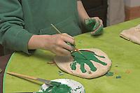 Kinder basteln Kacheln aus Salzteig, Handabdruck auf Salzteig, Junge malt Satzteig-Abdruck seiner Hand an