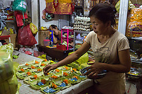 Bali, Indonesia.  Woman making Offerings (Canang) to Sell in the Early-morning Jimbaran Market.