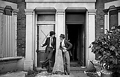 1977:  A squatter and a workman talk outside a house in Bravington Road being gutted following an eviction.  Many neighbouring houses were 'tinned up' and in very poor condition.  Bravington, Portnall and Ashmore Road became a Housing Action Area in 1978.