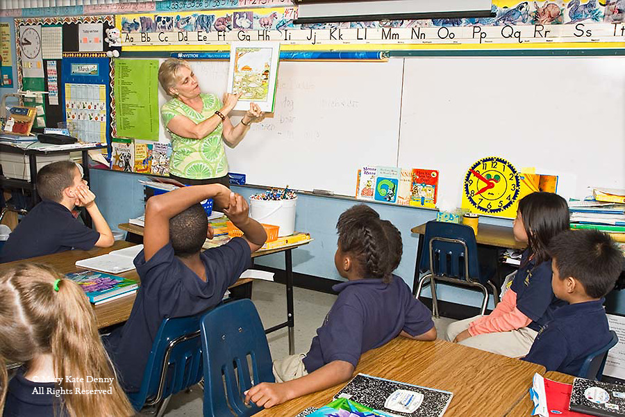 Caucasian teacher points out picture in book telling a story to a mixed ethnic group of children in classroom in New Orleans, Louisiana