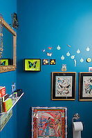 """On this wall painted a """"Biscay Bay"""" blue is displayed a collection of framed butterflies"""