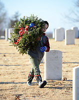 Knox McDaniel, 8, of Springdale carries wreaths Saturday, Jan. 9, 2021, while collecting the holiday wreaths at the Fayetteville National Cemetery. The wreaths were placed in front of each grave in the cemetery in December by volunteers through the Wreaths Across America program and were collected by groups of volunteers organized by the Fayetteville National Cemetery Advisory Council who worked in shifts because of the pandemic. Efforts in the past to recycle the metal in the wreaths did not attract enough volunteers to continue to make the effort feasible, so the wreaths had to be discarded. Visit nwaonline.com/210110Daily/ for today's photo gallery. <br /> (NWA Democrat-Gazette/Andy Shupe)