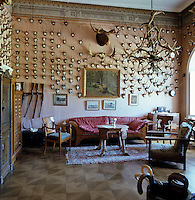 Hunting trophies cover the walls of the gun room which is furnished with a Biedermeier sofa, a coffee table fashioned out of hooves and a chandelier of antlers