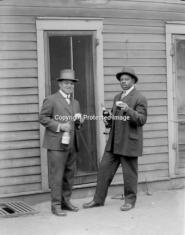 """SHARING A DRINK--OR A JOKE? In one image, two friends appear to toast the viewer with a favorite beverage. In the matching view, the same gentlemen pose with casual dignity. Several series of John Johnson photographs raise questions as to their exact purposes, while some were clearly posed as jokes. The man at left in these views may be Clayton Lewis, a star athlete at Lincoln High School who graduated in 1922 and married Dorothy Loving (see image LB200). Clayton (1903-1967) worked as a """"red cap"""" (porter) for the Chicago, Burlington and Quincy Railroad, then for many years was employed by the Lincoln Water Department before moving to Los Angeles in 1960.<br /> <br /> Photographs taken on black and white glass negatives by African American photographer(s) John Johnson and Earl McWilliams from 1910 to 1925 in Lincoln, Nebraska. Douglas Keister has 280 5x7 glass negatives taken by these photographers. Larger scans available on request."""