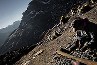 Pallaquera, a female gold miner, searches for gold on a load of waste rock from the gold mines in La Rinconada, Peru, 3 August 2012. During the last decade, the rising price of the gold has attracted thousands of people to La Rinconada in the Peruvian Andes. At 5300 metres above sea level, nearly 50.000 people work in the gold mines and live in the nearby colonies without running water, sewage system or heating service. Although the work in the mines is very dangerous (falling rocks, poisonous gases and a shifting glacier), the majority of miners have no contract and operate under the cachorreo system - working 30 days without payment and taking the gold they supposedly find the 31st day as the only salary. In spite of a demaged environment, caused by mercury contamination from the mining and the lack of garbage disposal, people continue to flock to the region hoping to find their fortune.