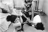 """USA. New York City. Spanish Harlem. Chichi (L), Lady and Bente (R), three sisters play together on a bed. Teddy bear. The Puerto Rican family lives below the poverty line and receives public assistance (AFDC, Home Relief, Supplemental Security Income and Medicaid). The family resides in units managed by the New York City Housing Authority (NYCHA) which provides housing for low income residents. NYCHA administers rental apartments in facilities, popularly known as """"projects"""". Spanish Harlem, also known as El Barrio and East Harlem, is a low income neighborhood in Harlem area. Spanish Harlem is one of the largest predominantly Latino communities in New York City. 20.06.88 © 1988 Didier Ruef .."""