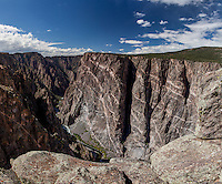 The rock formation named The Painted Wall with blue sky and clouds over the rock formation and the Gunnison River flowing below at Black Canyon of the Gunnison National Park in Colorado.