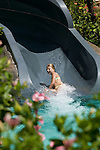 A young girl goes down the water slide.