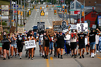 Protest organizer, Camille Redman, leads the group as they march through Brentwood from the Giant Eagle along Route 51 in honor of Jonny Gammage on his birthday, who was killed by police in 1995, on Monday July 20, 2020 in Pittsburgh, Pennsylvania. (Photo by Jared Wickerham/Pittsburgh City Paper)