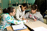 Education Elementary school Grade 5 class with science specialist making models from toothpicks and mini marshmallows 3 female students working together drawing plan on paper horizontal
