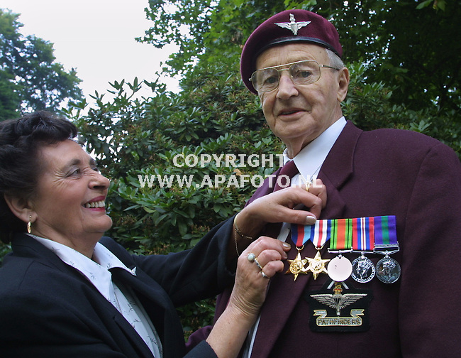 oosterbeek 310801 trots speldt zijn vrouw deze oorlogsvetraan zijn nieuwe medailles op, de oude waren gestolen. dankzij onze lezers kan hij morgen de airbornemars met medailles lopen.<br />foto frans ypma APA-foto
