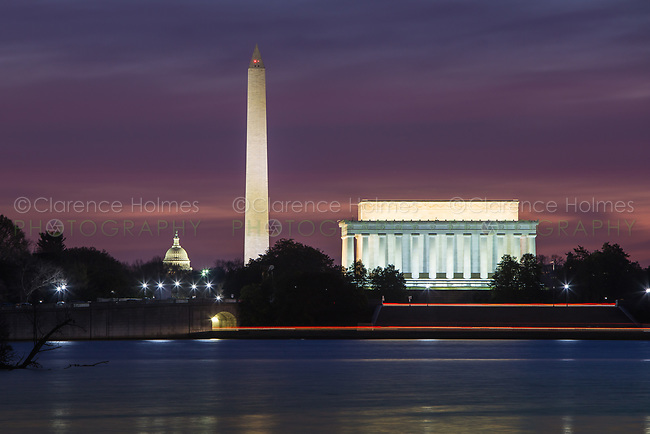 The Lincoln Memorial, Washington Monument, and US Capitol building set against an magenta sky during morning twilight in Washington, DC.