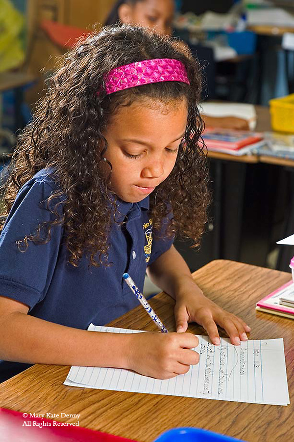 Seven year old mixed black female in uniform writes on lined paper at desk in classroom in New Orleans