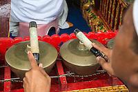 Jatiluwih, Bali, Indonesia.  Member of a Gamelan Orchestra Playing the Kempli (Gong),  Luhur Bhujangga Waisnawa Hindu Temple.