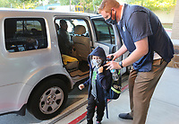 John Gourlay, director of development at The New School, helps () with his back pack Thursday, October 1, 2020, as he enters the school for a day of classes in Fayetteville. Check out nwadg.com/photos for a photo gallery.(NWA Democrat-Gazette/David Gottschalk)