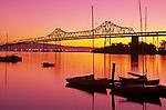 Retro Image of San Francisco Oakland Bay bridge at sunrise and small marina with sailboats silhouetted San Francisco, California USA