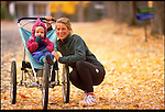 mother and daughter with jog-stroller in autumn
