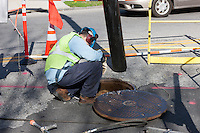 A Con Edison crew member works by a manhole on a street in White Plains, New York