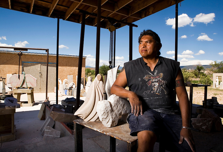 Artist Cliff Fragua with some unfinished pieces at this workplace, Singing Stone Studio, in Jemez Pueblo. Because of the dust created by grinding the stone, half of his studio is open to the outdoors, surrounded by views of the mountains.