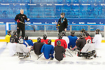 Sochi, RUSSIA - Mar 1 2014 -  Assistant Coach Curtis Hunt and Head Coach Mike Mondin gives instructions to the team during their first practice before the 2014 Paralympics in Sochi, Russia.  (Photo: Matthew Murnaghan/Canadian Paralympic Committee)