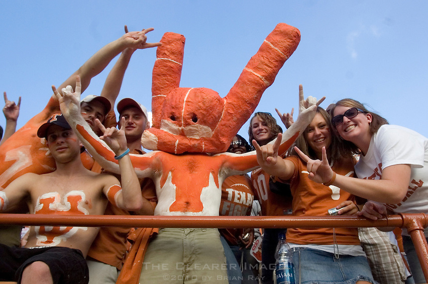 """09 September 2006: Danny Weisman (center), a sophomore chemical engineering major from Cleveland, Ohio, cheers with other fans from inside his paper mache """"hook'em horns"""" face mask/helmet during the Longhorns 24-7 loss to the Ohio State Buckeyes at Darrell K Royal Memorial Stadium in Austin, TX."""
