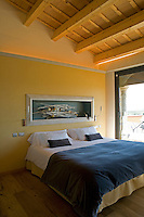A guest bedroom features a recessed niche displaying a natural sculpture above the bed in the five star hotel, Can Bonastre