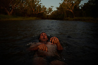 Nick and Joanna Atkins pull up for the night close to a river crossing on the corrugated Gibb River Road at Carson River Road. The couple bathe and take a well-earned break in the last light of the day and keep a nervous eye out for crocodiles.