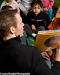 Preschool 3-5 year olds male teacher reading to group of children