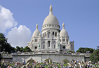 Montmartre, Paris. Basilica Sacre Coeur with tourists on green lawn
